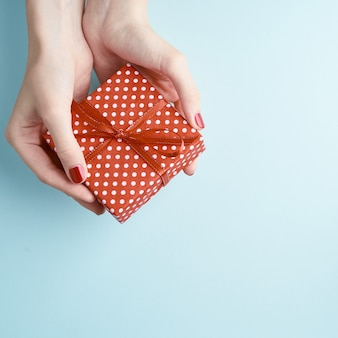 Woman hands holding red gift with ribbon