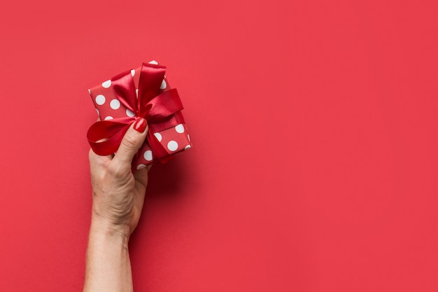 Woman hands holding red giftbox with red bow on grey background