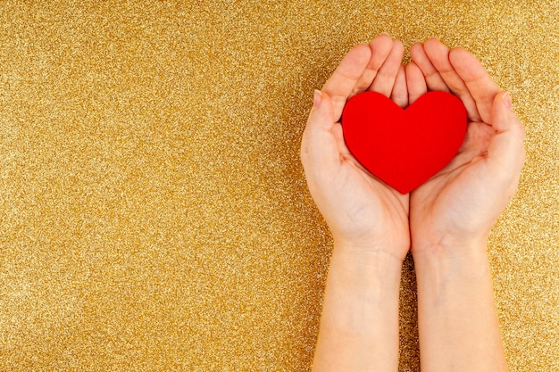 Woman hands holding red heart on gold background - health care, love