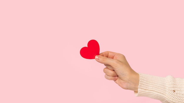 Женщина руки держит красное сердце на розовом фоне