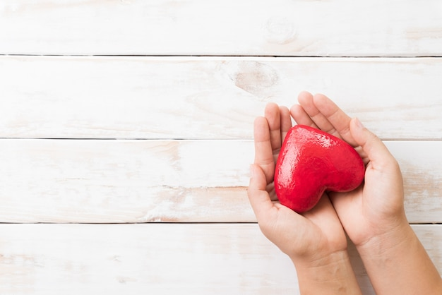 Woman hands holding red heart on white wooden background.