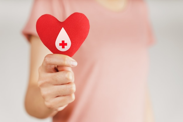 Женщина руки держит красное сердце с знаком донора крови. концепция здравоохранения, медицины и донорства крови