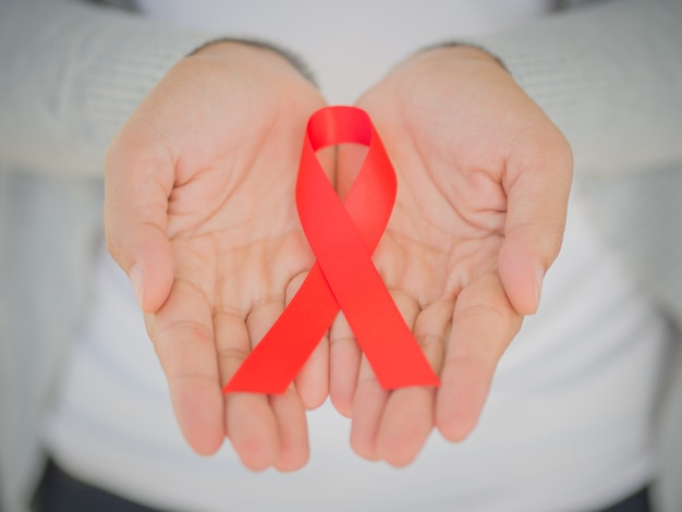 Woman hands holding red ribbon hiv, world aids day awareness.