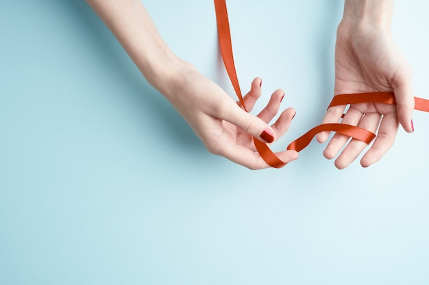 Woman hands holding red ribbon