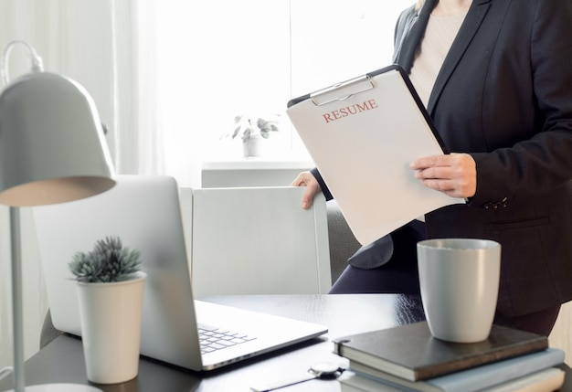 Woman hands holding resume application near her workplace with laptop.