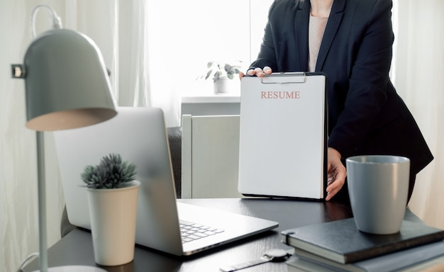 Женщина руки, держа приложение резюме рядом с ее рабочим местом с ноутбуком.