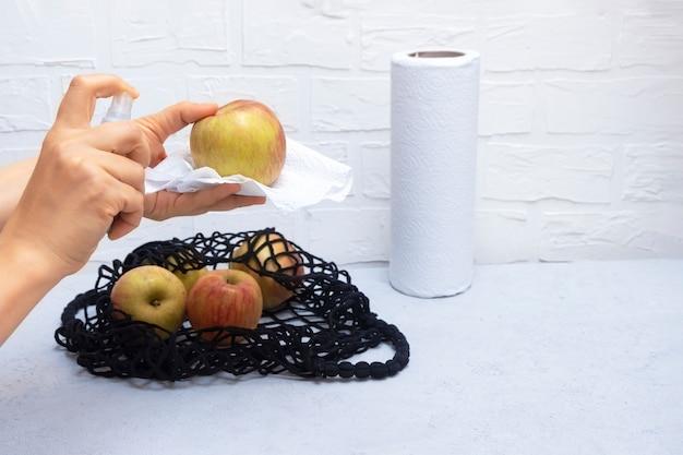 消毒剤を押しながらテーブルの上のメッシュバッグが付いている台所で食料品を洗浄する女性の手