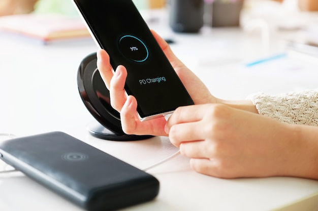 여자 손에 pd 충전 기술을 사용하여 외부 전원 은행에서 스마트 폰 충전 배터리를 들고