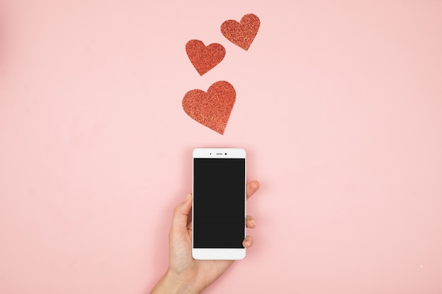 Woman hands holding smartphone on pink surface with copy space. flat lay. top view. mockup template for valentines day.