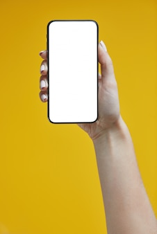 Woman hands holding smartphone on yellow .
