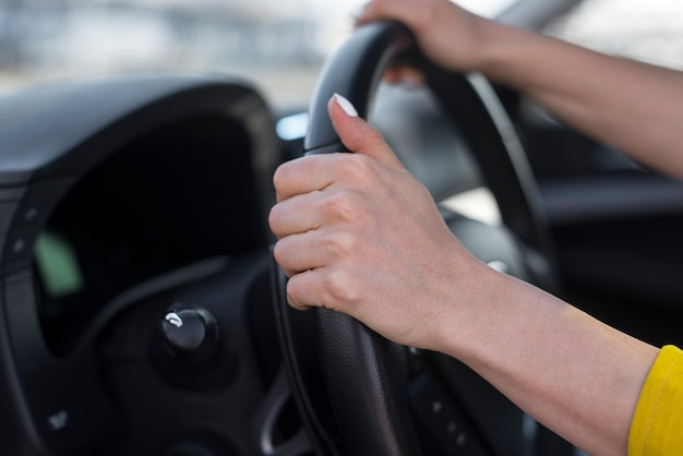 Woman hands holding the steering wheel