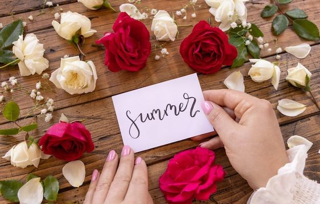 여자 손에 나무 테이블에 꽃 근처 여름 카드를 들고 가까이