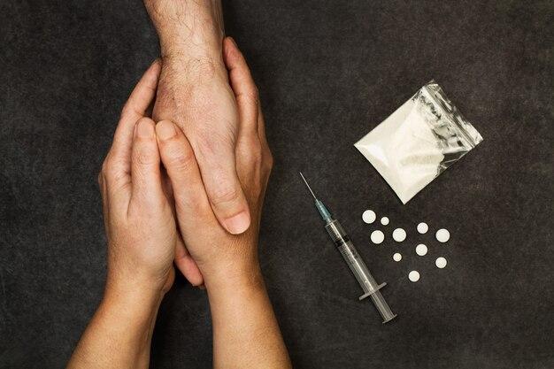 Руки женщины, держащие руку зависимого мужчины на темном фоне