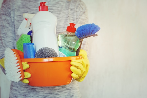 Woman hands holding tub with cleaning supplies.