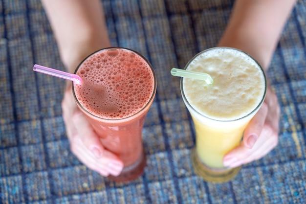 파인애플과 수박 신선한 주스가 든 두 잔을 들고 있는 여성의 손, 클로즈업, 건강한 생활 방식 개념