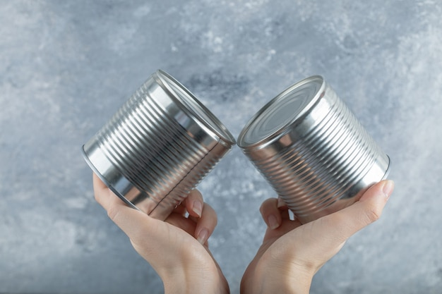 Woman hands holding two metallic cans on marble.