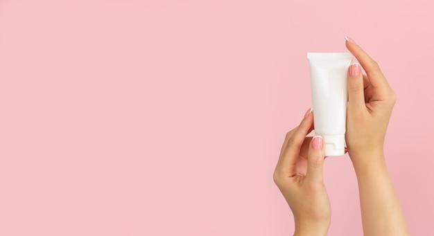 분홍색 배경에 브랜드가없는 플라스틱 화장품 튜브를 들고 여자 손