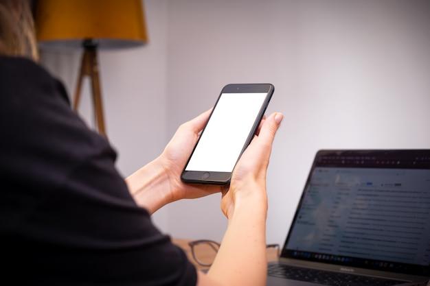 テーブルのオンラインショッピングでラップトップと自宅でスマートフォンを使用して保持している女性の手