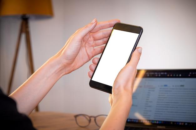 自宅でスマートフォンを使用して保持している女性の手