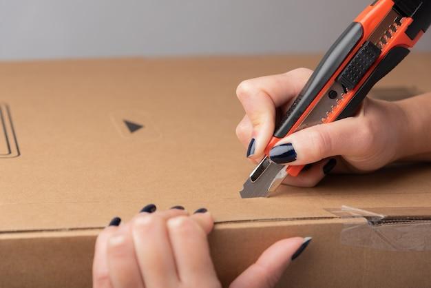 テキストやデザインのようなチュートリアルの説明のための空のスペースでカートンボックスの上にユーティリティナイフを保持している女性の手