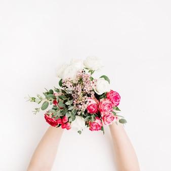 白、ピンク、赤のバラ、ユーカリの枝、白い背景に野生の花を持つウェディング ブーケを持つ女性の手。フラットレイ、トップビュー
