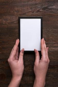 Женщина руки, держа белую рамку на деревянном фоне. подвешивание аттестата или диплома