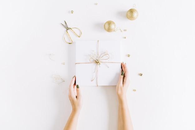 弓で白いギフト ボックスを保持している女性の手。クリスマス フラット レイアウト、トップ ビュー
