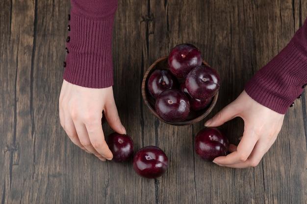 Mani della donna che tengono una ciotola di legno con prugne viola sane.