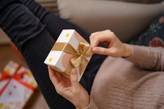 Mani della donna che tengono scatola bianca avvolta con fiocco dorato, concentrarsi sulla scatola