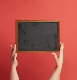 Woman hands holds brown empty wooden frame on red space