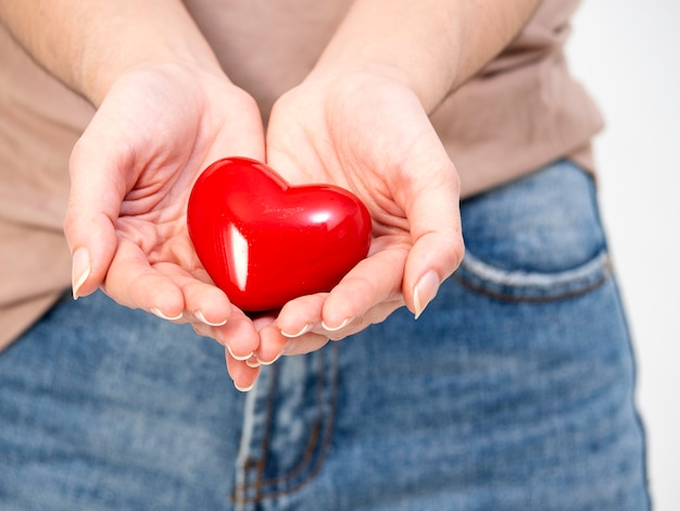 Woman hands holds red heart