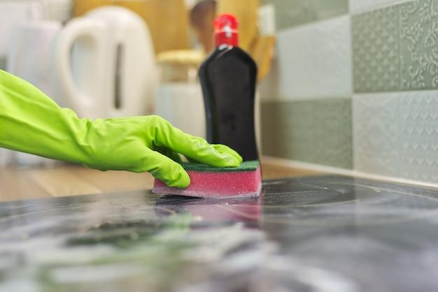 手袋をはめた女性がスポンジと洗剤でキッチンの電気セラミックコンロを掃除する
