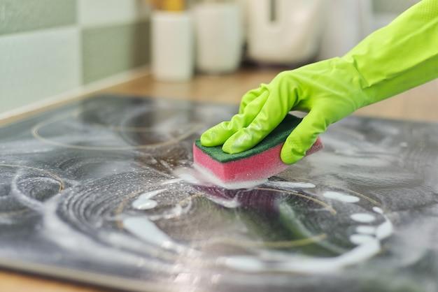 장갑을 끼고 있는 여성은 주방 전기 세라믹 호브를 스폰지와 세제로 청소합니다