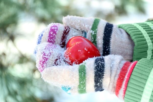 冬の背景に赤いハートを保持しているニットミトンを手に女性