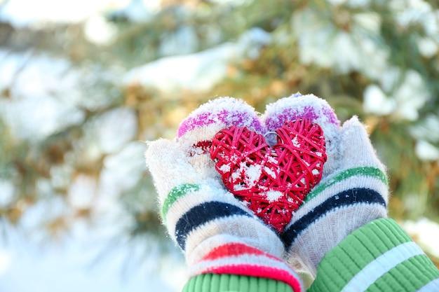 冬に赤いハートを持ってニットミトンを手に女性