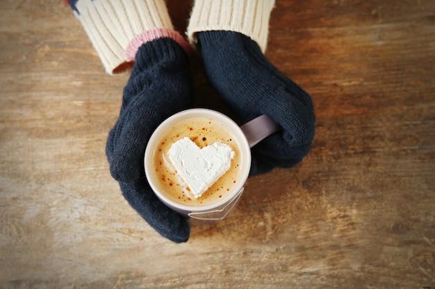 Женщина руки в рукавицах, держа чашку кофе