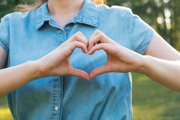 여자는 심장의 모양에 손을. 건강, 사랑 및 돌보는 개념