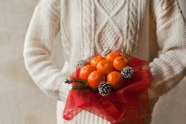여자는 만다린과 크리스마스 나무 가지의 꽃다발을 들고 흰색 스웨터에 손을. 새해의 식용 과일 꽃다발. 크리스마스 선물. diy 선물. 과일로 만든 유용한 선물. 과일 장식.