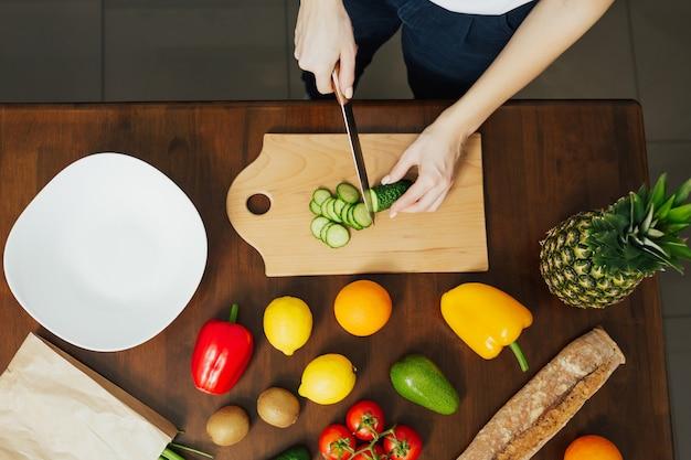女性の手は木製のまな板で野菜を切っています