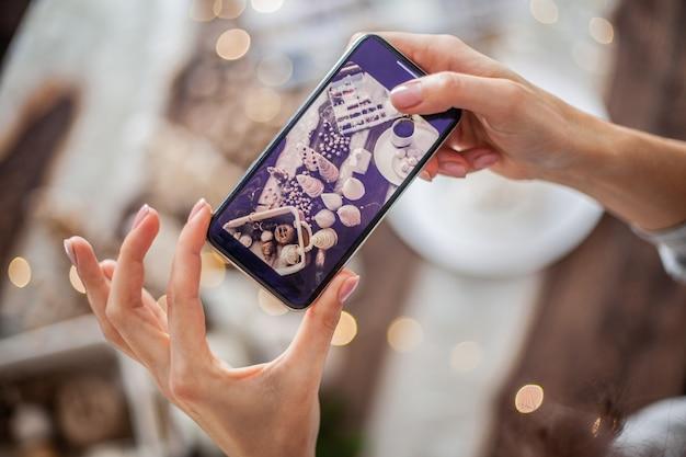 여자 손 손수 크리스마스 트리 콘으로 크리스마스 구성을 휴대 전화에서 사진을 찍고 전화 설정을 사전 설정 및 필터로 사용하고 있습니다.