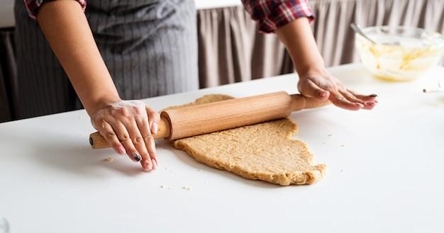キッチンで生地をこねる女性の手