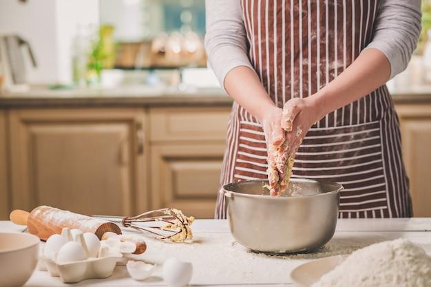 鉄のボウルで生地をこねる女性の手。縞模様のエプロンを着た女性がキッチンで料理をしている
