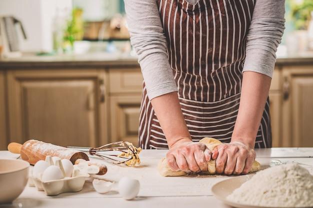 台所のテーブルの上で生地をこねる女性の手。縞模様のエプロンを着た女性がキッチンで料理をしている