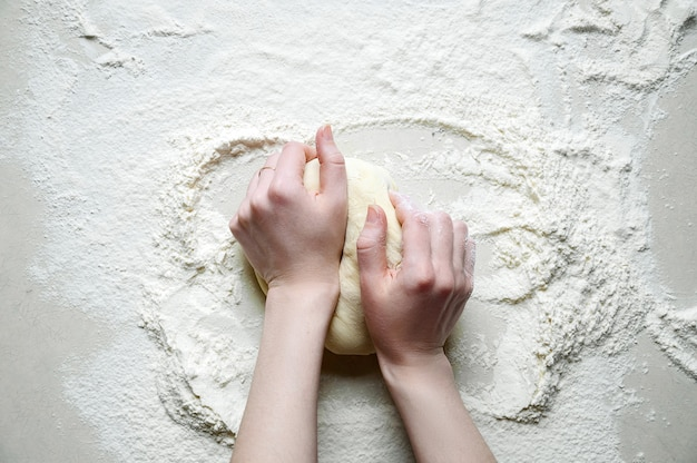 Woman hands kneads the dough with flour on the white kitchen table. top view flat lay.