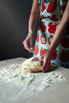 여자 손 반죽을 반죽 하 고 식탁에 흰 밀가루로 뿌리십시오. 어둠 속에서 테이블에 빔 라이트 폭포