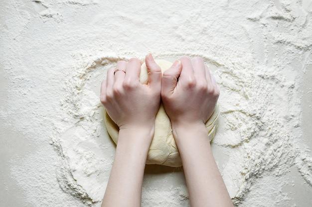 Женщина руки замешивает тесто с мукой на белом кухонном столе. вид сверху плоская планировка.