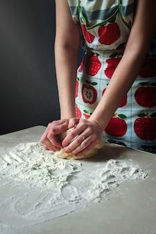 여자 손 식탁에 흰 밀가루 반죽을 반죽. 어둠 속에서 테이블에 빔 라이트 폭포