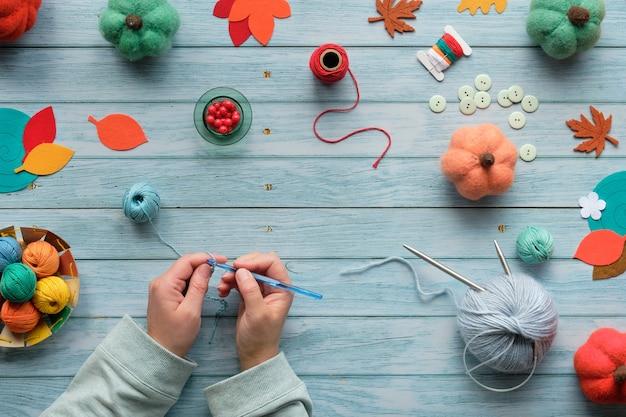 女性の手編みかぎ針編み。糸のボール、ウールの束、装飾的なカボチャ、秋の紅葉と木製のテーブルの平面図です。