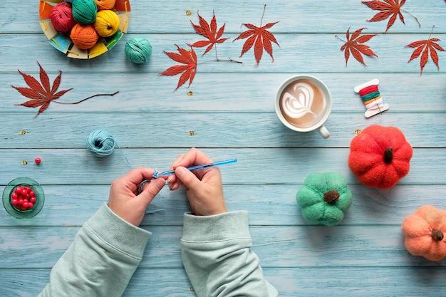 女性の手編みかぎ針編み。糸のボール、ウールの束、装飾的な秋のカボチャ、秋の紅葉の平面図です。