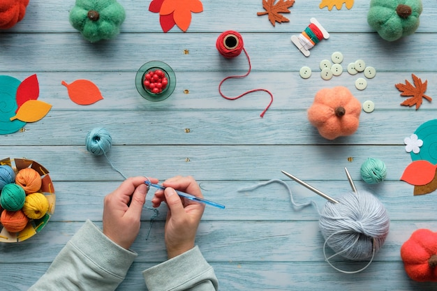 Woman hands kniting crochet. top view of the wooden table with yarn balls, wool bundles, decorative pumpkins, autumn leaves.